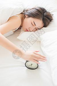 年轻女性起床困难按闹钟图片