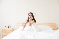 年轻女性醒来坐床上图片
