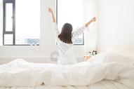年轻女性坐床边伸展背影图片