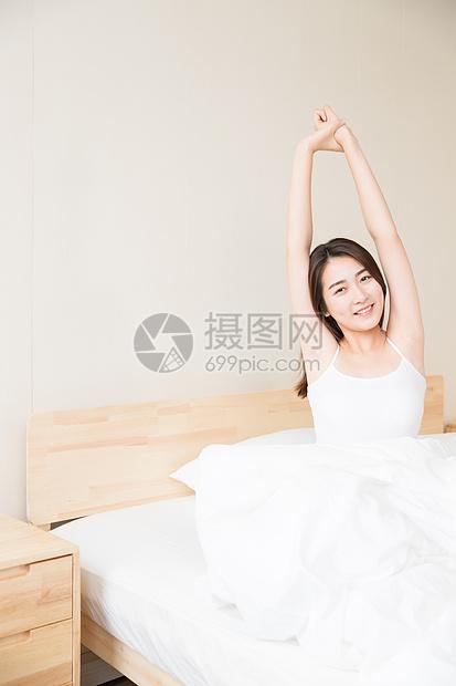 年轻女性起床床上伸展图片
