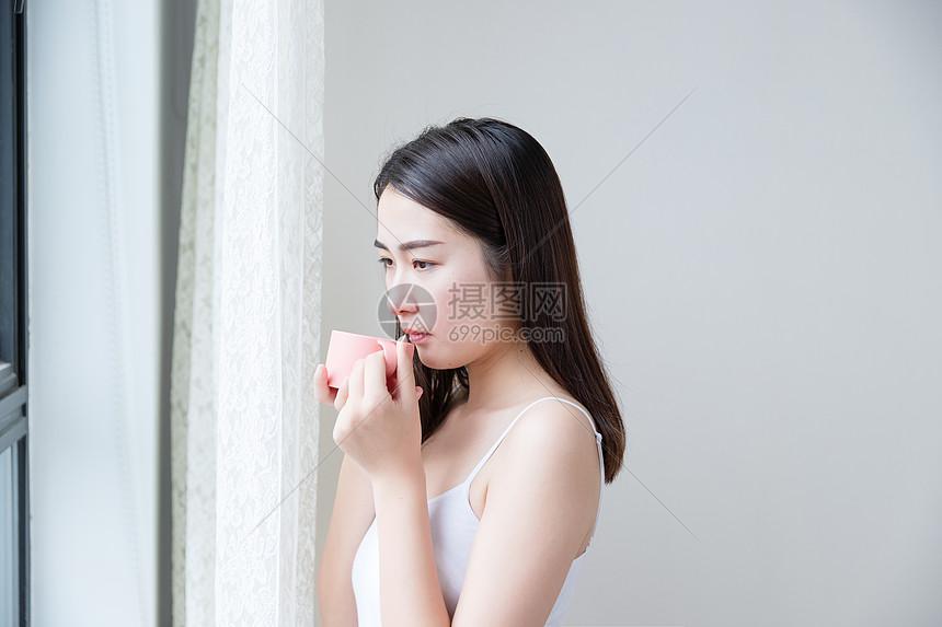年轻女性窗边喝水图片