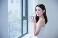 年轻女性窗边喝水501071687图片