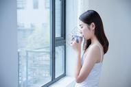 年轻女性窗边喝水501071688图片