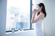 年轻女性窗边喝水501071691图片