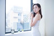 年轻女性窗边喝水501071692图片