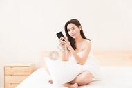 年轻女性床上休息看手机图片