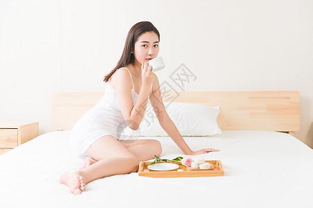 年轻美女在床上吃早餐图片