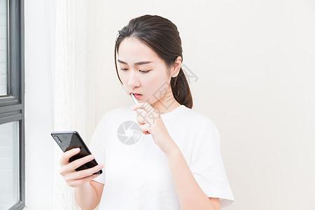 年轻女性刷牙看手机图片