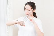 年轻女性刷牙看手表图片