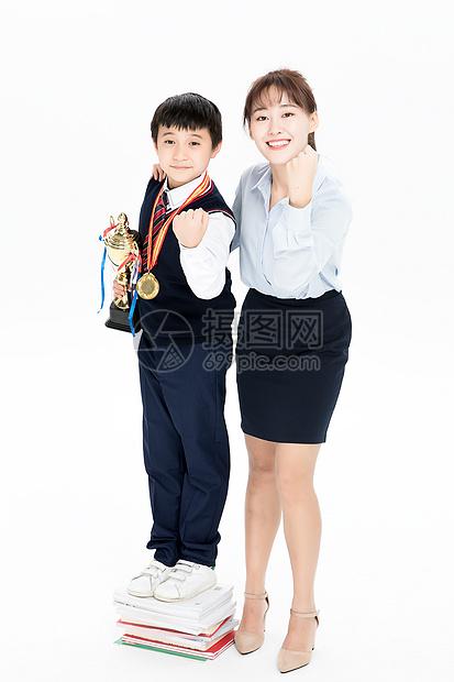 拿奖杯的小学生和老师合影图片