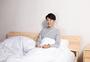 躺在床上玩手机的男性图片