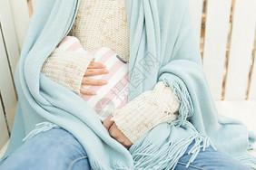 女生抱暖手袋特写图片