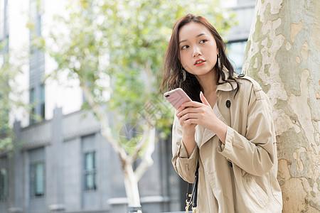 年轻女性拿手机等候图片