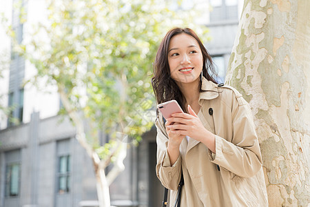 年轻美女拿手机微笑图片