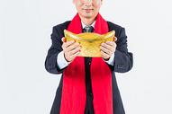 新春商务男性手拿金元宝特写图片