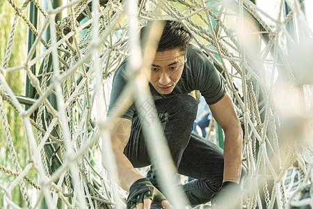 户外男性攀爬绳梯训练图片