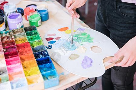 女性绘画调颜料特写图片