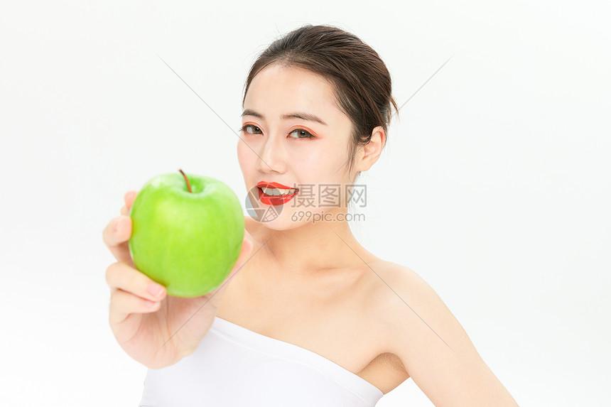 拿青苹果的美女图片
