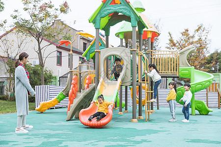 户外幼师带儿童玩滑滑梯图片