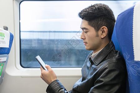 男性在车厢玩手机图片
