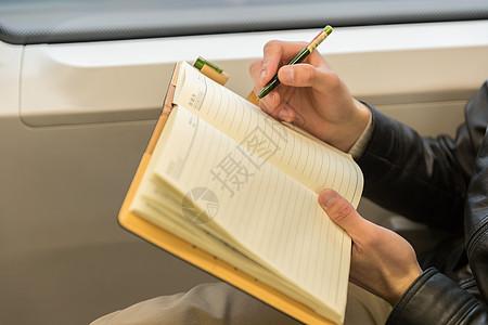 男性在车厢内记笔记图片