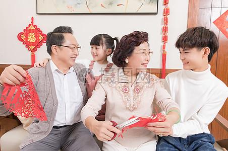 春节爷爷奶奶教孩子剪窗花图片