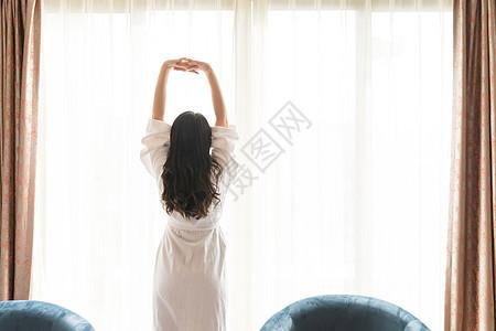 年轻女性酒店客房伸展背影图片