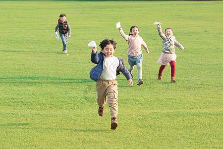 草地上玩纸飞机的孩子们图片
