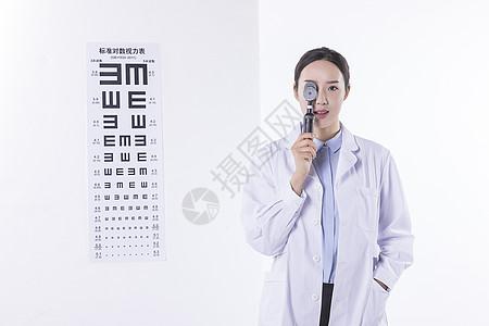 手拿眼底镜的眼科医生图片