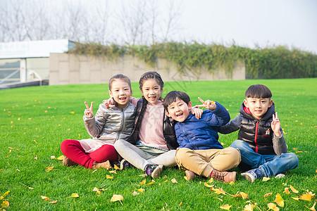 儿童坐在草坪上玩耍图片