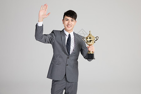 商务男士手拿奖杯图片