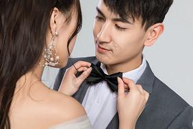 年轻妻子为丈夫系领结图片