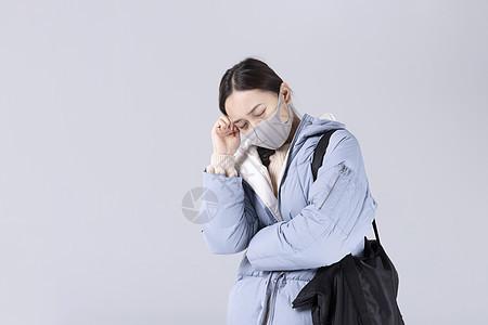 戴着口罩头疼的女孩图片