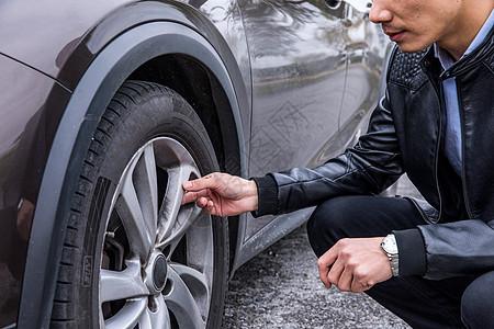 男性检查汽车轮胎图片