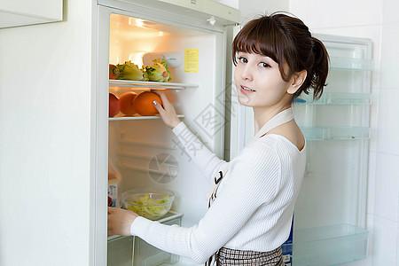 从冰箱里拿蔬果的家庭主妇图片