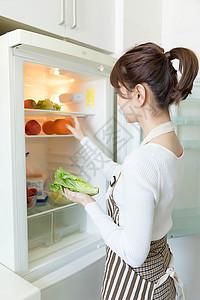 从冰箱里拿果蔬的家庭主妇图片