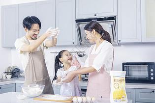 一家三口家庭烘培揉面粉图片