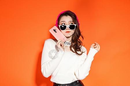 时髦女生拿手机思考图片
