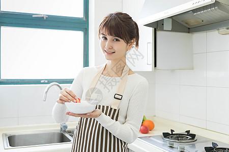 在厨房做早餐的家庭主妇图片