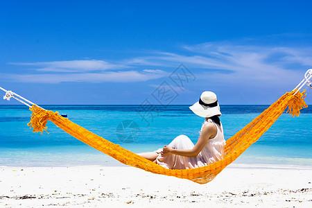 坐在吊床上的海滩美女图片