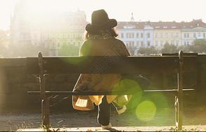 坐在布拉格伏尔塔瓦河边的女子背影图片