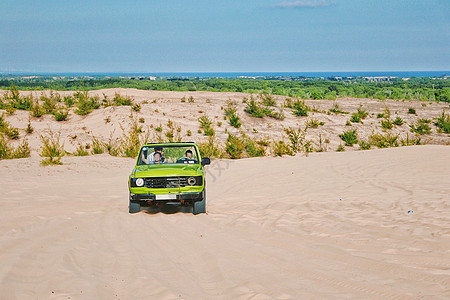 越南美奈白沙丘上疾驰的越野车图片