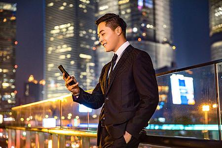 年轻商务男子天桥玩手机图片