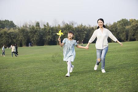 女儿和妈妈拿着风车在草坪上奔跑图片