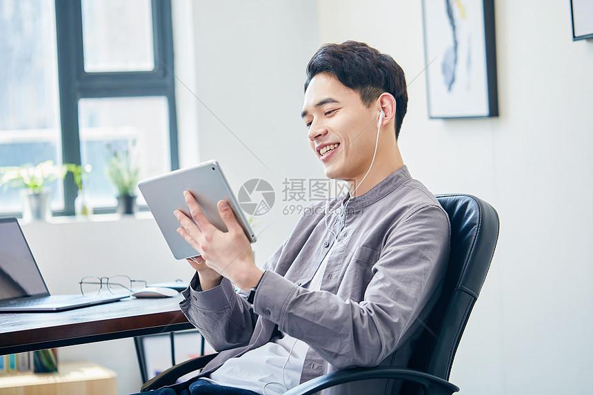 年轻男士使用平板电脑办公图片