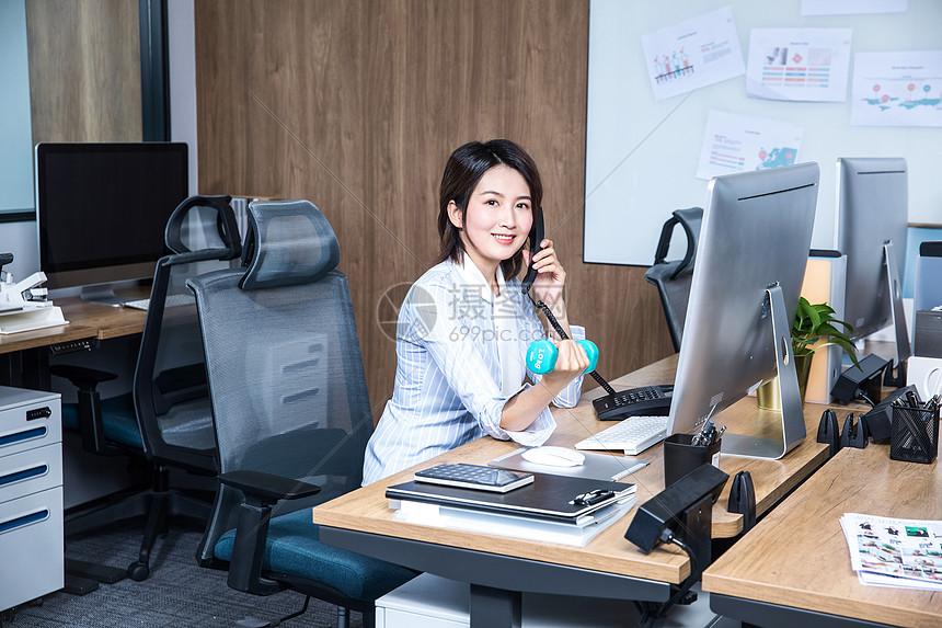 女性办公室打电话锻炼哑铃图片