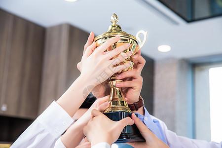企业团队高举奖杯图片