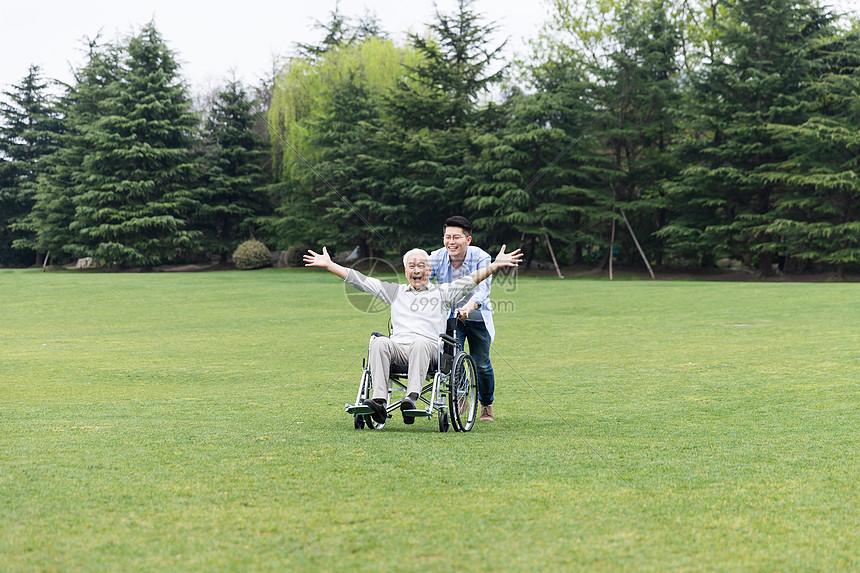 老年父子开心推轮椅图片