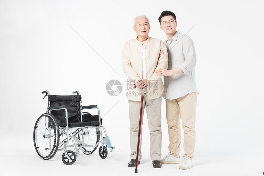 老年人父子搀扶站立图片