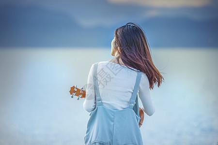 女孩休闲看海弹吉他背景图片